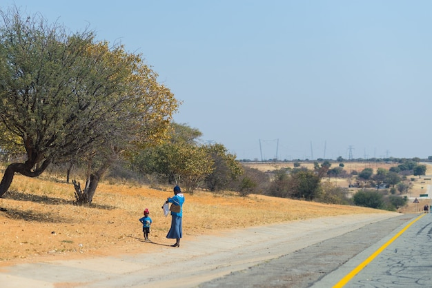Arme mensen lopen langs de weg in namibië, afrika.