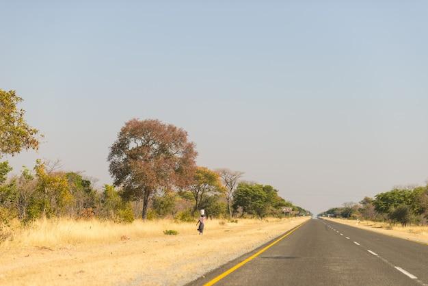 Arme vrouw die langs de kant van de weg in de landelijke caprivi-strook loopt, het dichtstbevolkte gebied in namibië, afrika.