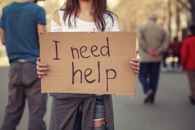 Arme vrouw die op straat om hulp smeekt