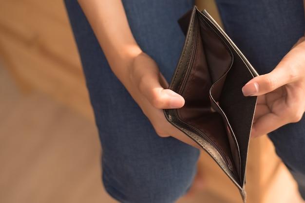 Arme vrouw zonder geld in een lege portemonnee