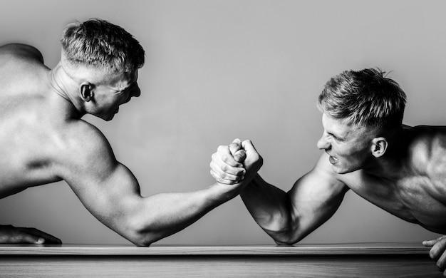 Armworstelen. twee mannen armworstelen. rivaliteit, close-up van mannelijke arm worstelen. twee handen. zwart en wit. mannen die krachten meten, armen. handworstelen, strijden.