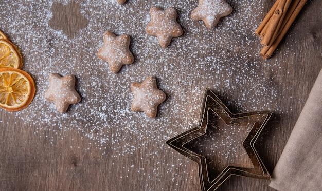 Aroma kerst peperkoek sterren met sinaasappel en kaneel in poedersuiker op een oude houten bruine tafel. zelfgemaakte cake. bovenaanzicht