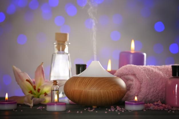 Aroma olie diffuser en kaarsen op onscherpe achtergrond