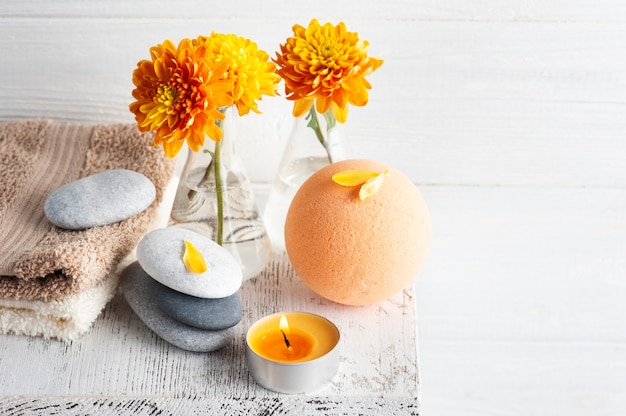 Aromabadbom in kuuroordsamenstelling met oranje bloemen en kiezelstenen. aromatherapie arrangement, zen stilleven met aangestoken kaarsen