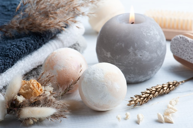 Aromabadbommen in kuuroordsamenstelling met droge bloemen en handdoeken. aromatherapie arrangement, zen stilleven met grijs aangestoken kaars en lichaamsborstels