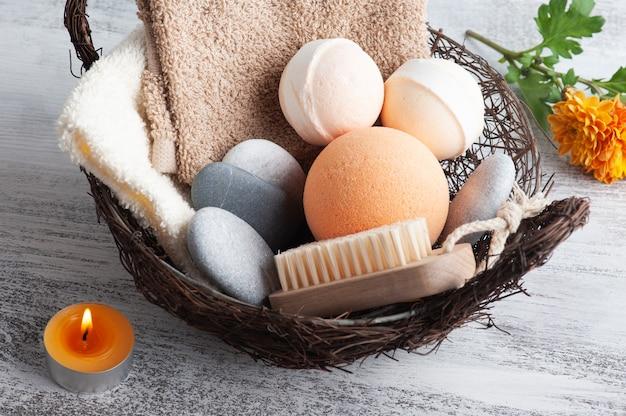 Aromabadbommen in kuuroordsamenstelling met oranje bloemen en borstel. aromatherapie arrangement, zen stilleven met aangestoken kaarsen