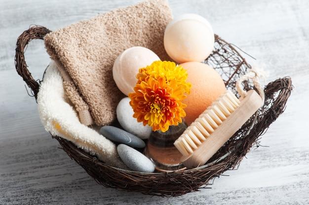 Aromabadbommen in kuuroordsamenstelling met oranje bloemen en borstel. aromatherapie arrangement, zen stilleven met lichtjes