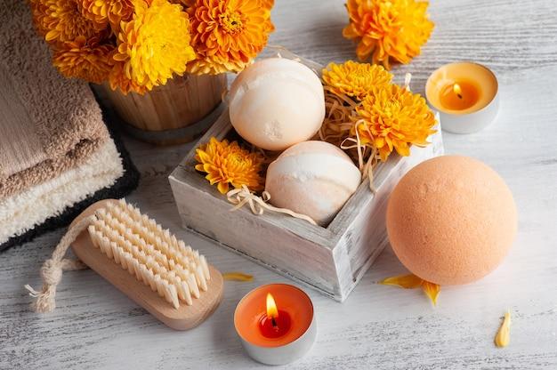 Aromabadbommen in kuuroordsamenstelling met oranje bloemen en handdoeken. aromatherapie arrangement, zen stilleven met aangestoken kaarsen