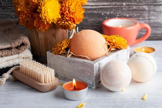 Aromabadbommen in kuuroordsamenstelling met oranje bloemen en handdoeken