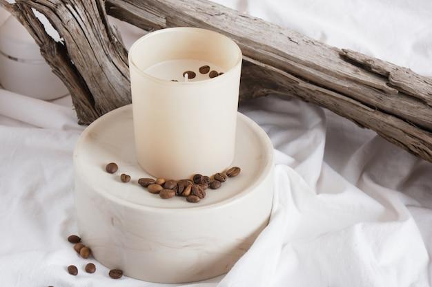 Aromakaars in glas op keramisch rond podium tegen een achtergrond van droog drijfhout. natuurlijke kaarsen witte doek achtergrond