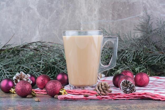 Aromakoffie met dennenappels en kerstballen op tafelkleed. hoge kwaliteit foto