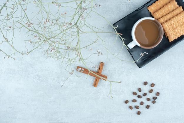 Aromakoffie met pijpjes kaneel en crackers op donkere plaat.