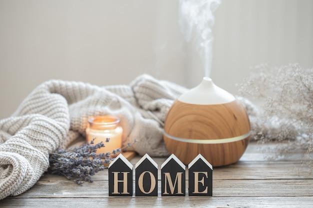 Aromastilleven met een moderne geuroliediffuser op een houten ondergrond met een gebreid element, knusse details en het decoratieve woord home.