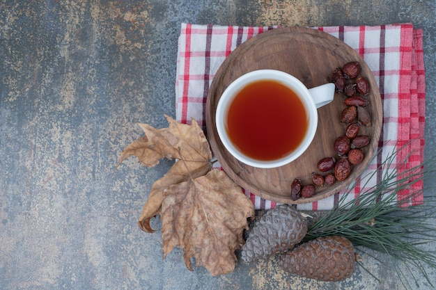 Aromathee in witte kop met rozenbottels en dennenappels op marmeren tafel
