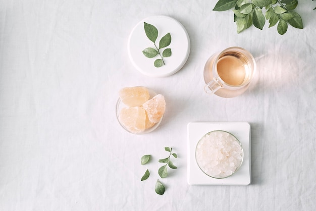 Aromatherapie. kleine glazen flesjes met cosmetische oliën. badzout. vers blad. objecten voor spa-procedures op witte achtergrond olie, blad.