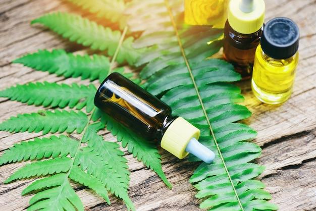 Aromatherapie kruidenolieflessen aroma met varenbladeren kruidenformuleringen, waaronder wilde bloemen en kruiden op hout - etherische oliën natuurlijk op houten en groen blad biologisch