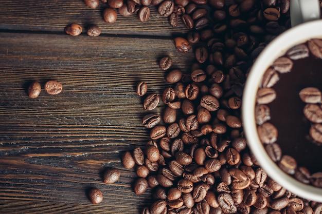 Aromatische drank in een kopje en koffiebonen verspreid over een houten achtergrond