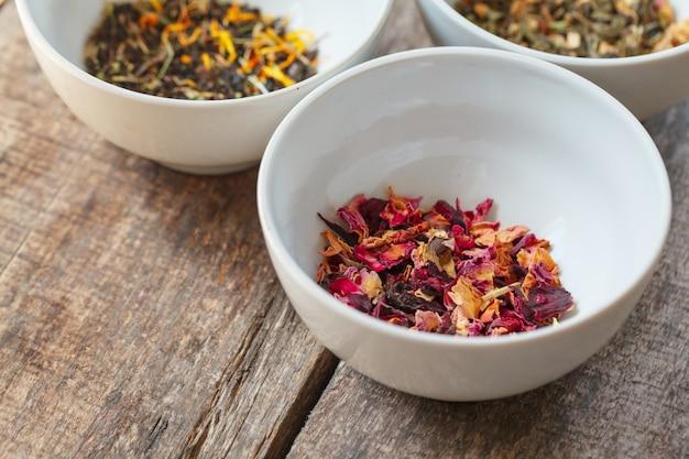 Aromatische droge thee in kommen op houten achtergrond