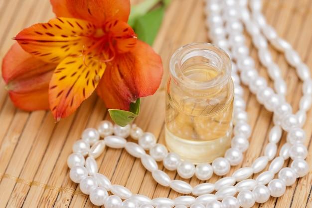 Aromatische etherische olie in kleine glazen flessen, alstroemeria bloemen en parelsparels