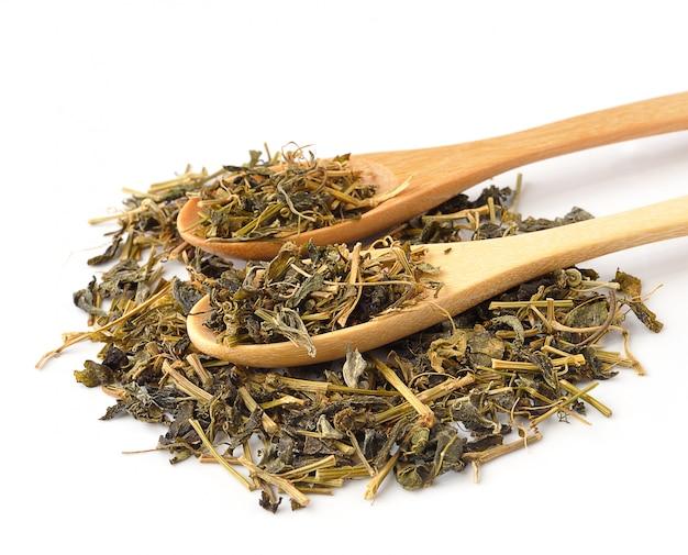 Aromatische groene droge thee in de lepel die op wit wordt geïsoleerd