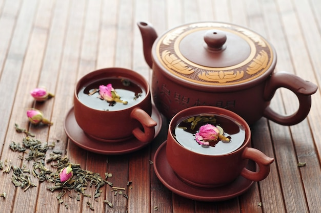 Aromatische groene thee met roze bloemen op houten oppervlak