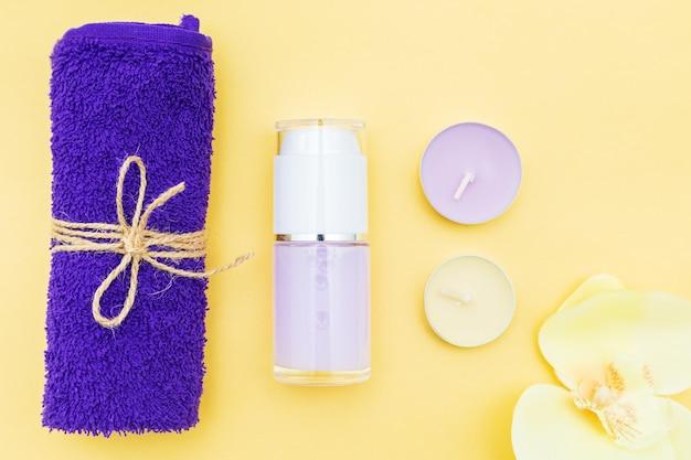 Aromatische kaarsen, handdoek en lotion op een gele achtergrond. bovenaanzicht, kopieer ruimte. spa-concept, plat gelegd.