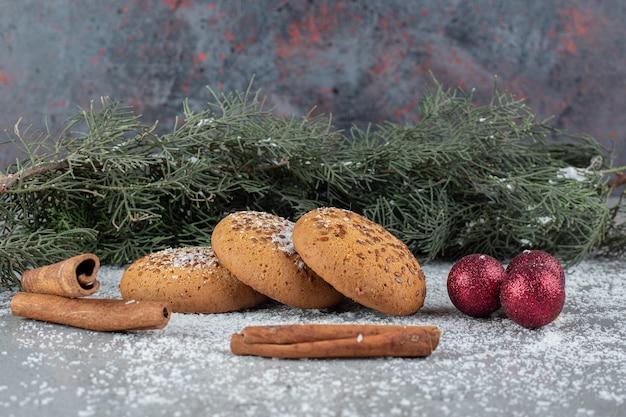 Aromatische kaneelstukjes, koekjes, decoratieve ballen en een tak op marmeren oppervlak