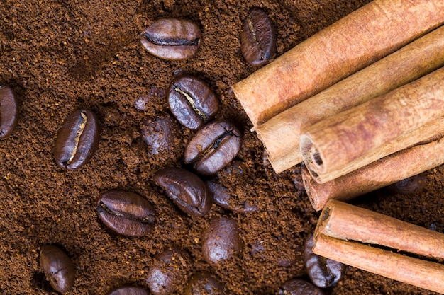 Aromatische koffie en kaneel op gemalen koffiepoeder, gehele pijpjes kaneel en koffiebonen en gemalen poeder, close-up