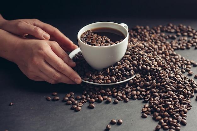 Aromatische koffiebonen op een grijze tafel en handen in de buurt van een kopje met een drankje