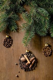 Aromatische kruidencollectie en verschillende koffiebonen in de vorm van kerstballen. piment, kaneelstokjes, kruidnagel, nootmuskaat geroosterde arabica bonen over donkere houten achtergrond. kerstgroetjes koffieliefhebbers