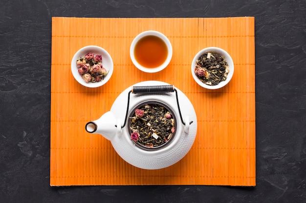 Aromatische kruidenthee en ingrediënt met witte keramische theepot op oranje placemat