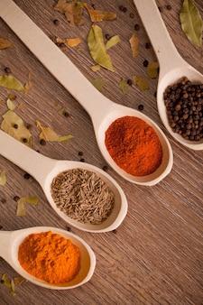 Aromatische poederkruiden op lepels in houten lijst