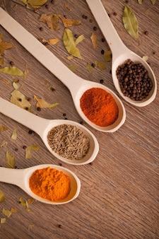 Aromatische poederkruiden op lepels in houten lijst Premium Foto