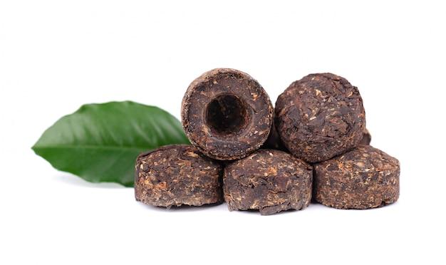 Aromatische zwarte pu-erh thee, geïsoleerd op wit