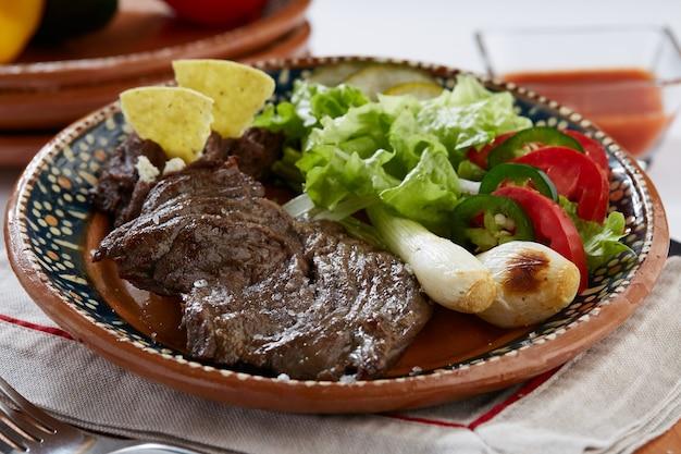 Arrachera con frijoles refritos cebollinas y ensalada servido en plato de barro