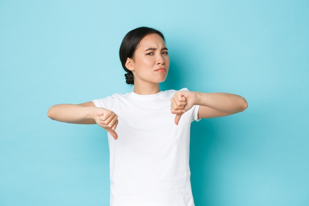 Arrogant, sceptisch en teleurgesteld aziatisch meisje deelt haar negatieve mening, grimassen en afkeurend hoofdschuddend, laat slechte opmerkingen achter, toont duimen naar beneden, ontevreden, blauwe muur.