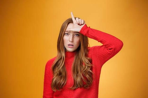 Arrogante en zelfvoldane roodharige vrouw vernederende persoon die een verliezer teken op het voorhoofd toont, spottende en minachtende rivaal die zelfverzekerd en snobistisch over oranje achtergrond staat