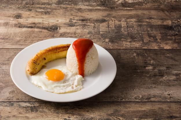 Arroz a la cubana typische cubaanse rijst met gebakken banaan en gebakken ei op een bord op houten tafel