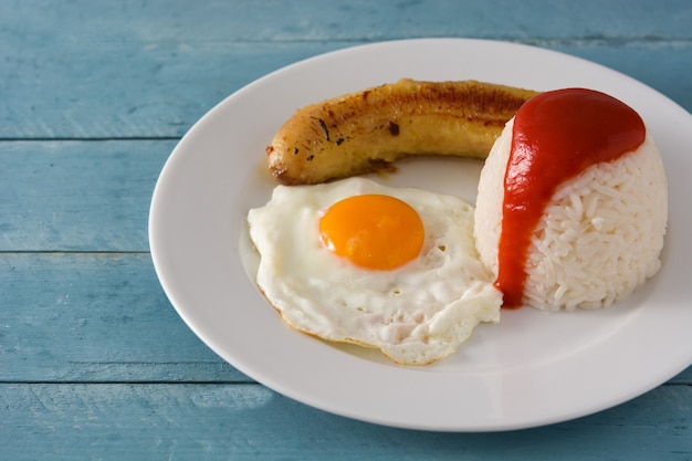 Arroz a la cubana typische cubaanse rijst met gebakken banaan en gebakken ei op een bord op houten tafel.