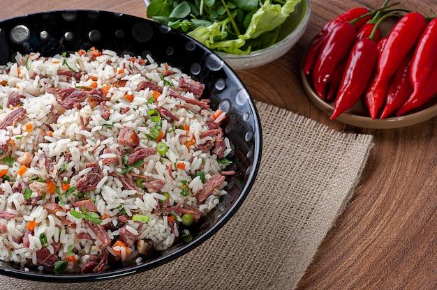 Arroz de carreteiro - typisch eten uit zuid-brazilië, gemaakt met rijst, gedroogd vlees, pepperoniworst, spek en wortelen. kopieer ruimte