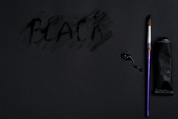 Art set van tube, zwarte verf geperst en tekst black handgeschreven met penseel op een donkere achtergrond. plat liggen.