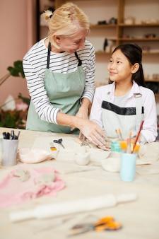 Art teacher helping asian girl