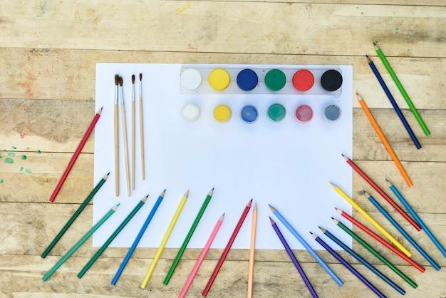 Art. veel kleurpotloden, penselen en potten met verf op een blanco vel papier. houten tafel