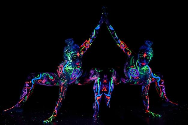 Art vrouw body art op het lichaam dansen in ultraviolet licht. heldere abstracte tekeningen op meisjeslichaam neonkleur