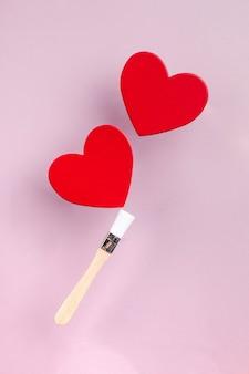 Artconcept van valentijnsdag wenskaarten twee rode harten op een kwastje op een roze achtergrond