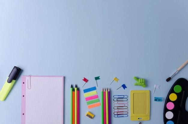 Artikelen voor school- en kantoorpotloden, notitieboekje, gummen, paperclips staan op een blauwe achtergrond.