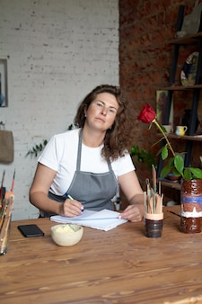 Artisanale vrouw die in notitieboekje schrijft en planning
