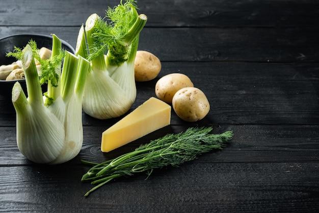 Artisjok met venkel, aardappel en parmezaanse kaas ingrediënten, op zwarte houten tafel