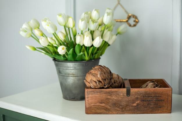 Artisjokbloemen in houten kist en een boeket witte tulpen in een vaas