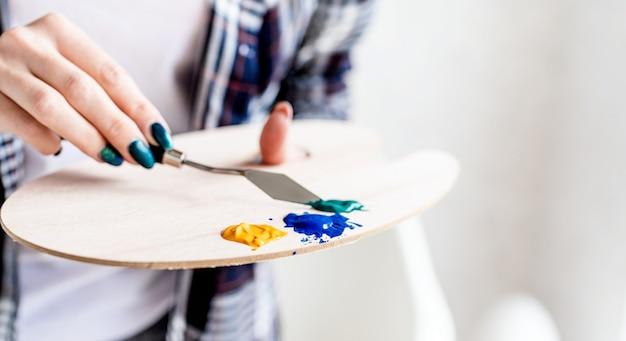 Artist palette kunstenaar handen mengen verf op het palet